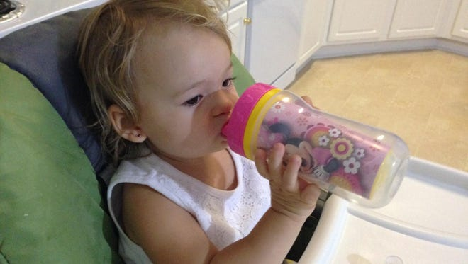 Isabella enjoys some apple juice in her sippy cup.