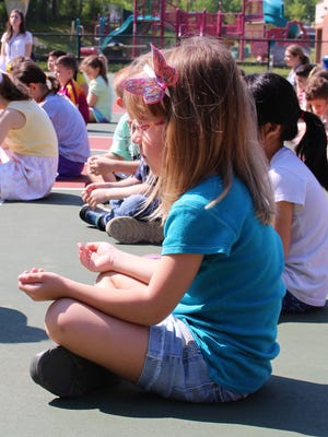 Kindergartner Abigail Ruffner participates in an outdoor mindfulness session on May 17 at Woodland School.