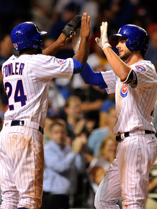 Chicago Cubs' Kris Bryant right, celebrates with teammate Dexter Fowler left, at home plate after Bryant hit a two-run home run during the seventh inning of a baseball game against the Cincinnati Reds on Wednesday, Sept. 21, 2016, in Chicago. (AP Photo/Paul Beaty)