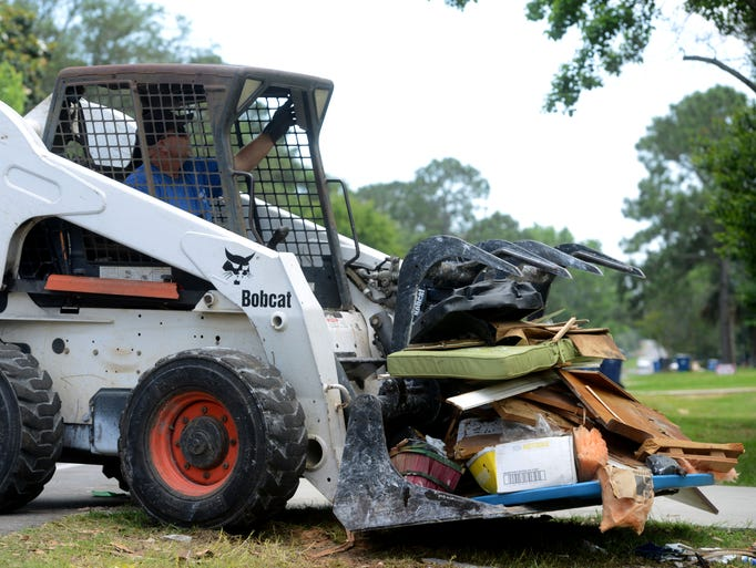 Erin Hurd, of Hurd Brothers Tree Care, picks up a load of flood debris from a home on Sunset Boulevard in Gulf Breeze before dropping it off at a holding site behind the Gulf Breeze Public Library.