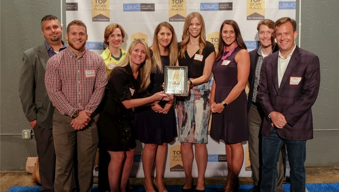 Premise Health team members accept the Top Workplaces award in 2017.