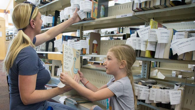 Tiffany Bruce and her 4-year-old daughter, Lauren, look for their reserved books at Gilbert's Southeast Regional Library. The town does not oversee the library. Instead, it contracts with Maricopa County to provide daily operations.