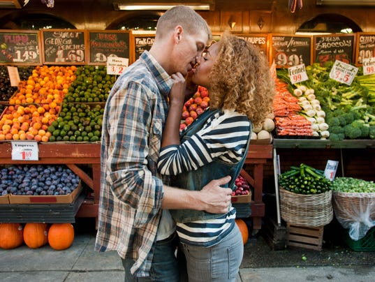 Couple kissing by market stall