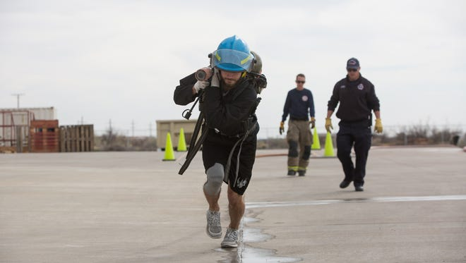 Angus Campbell, one of the goalies for the El Paso Rhinos runs the first part of the Las Cruces Fire Department's training course, a hose carrying drill at the LCFD training facility, Saturday, February 18, 2017.