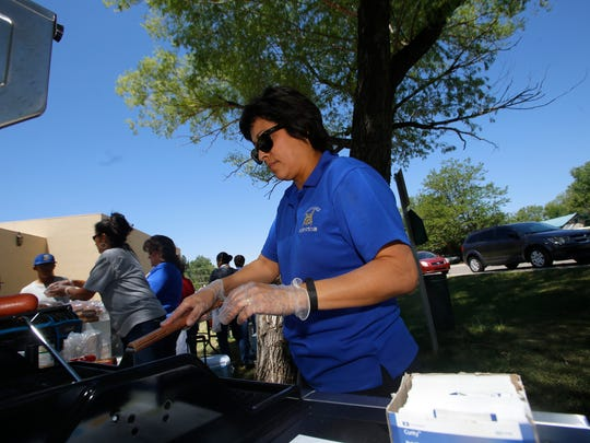 Bloomfield School District menu planner Joanne Rodriguez works the grill during a barbecue Tuesday in Bloomfield.