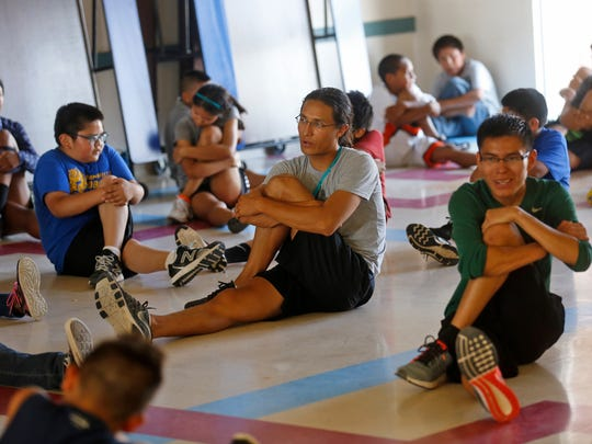 At center, Dustin Martin, program director with Wings of America's Running and Fitness Camp, leads students in a post-run stretch on Thursday at Ojo Amarillo Elementary School.