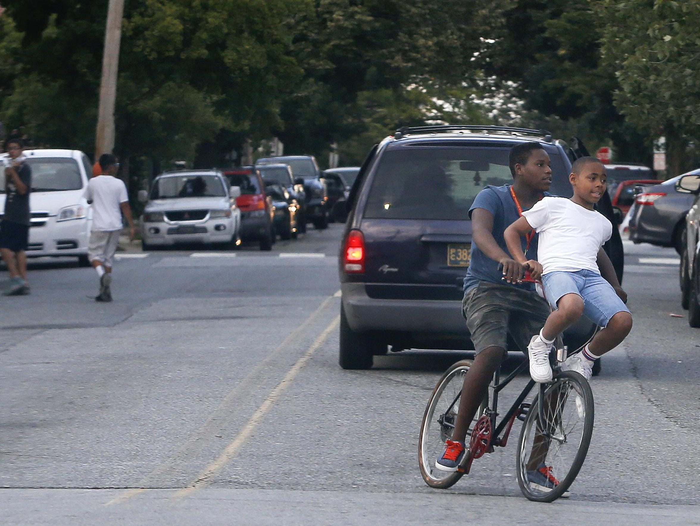 Young people share a bike ride on N. Scott Street in