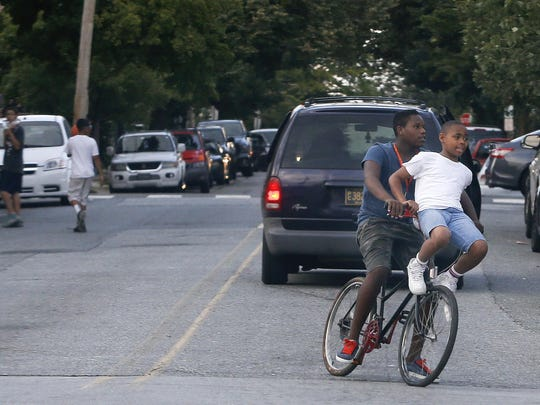 Young people share a bike ride on N. Scott Street in Wilmington early Wednesday evening.