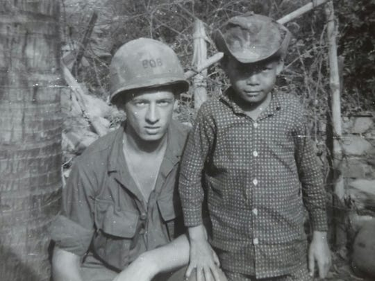 Robert Benson with a Vietnamese child during his time serving with the army in Vietnam.