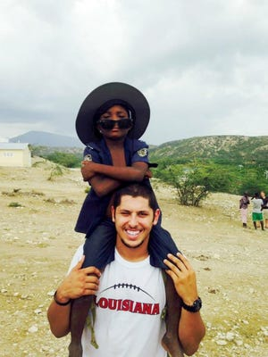UL starting quarterback Brooks Haack carries a young Haitian child on his shoulders during a recent mission trip to the country.