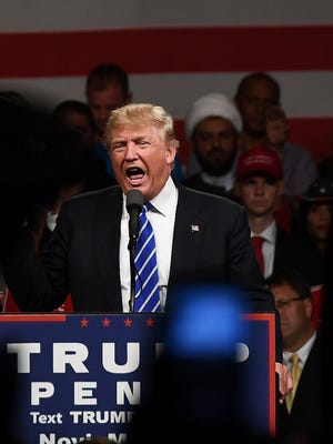 Sheikh Mohammad Hajj Hassan, a Shia Muslim leader (wearing a white turban), sits on stage behind Donald Trump on his left, at a Trump rally in Novi on Sept. 30, 2016