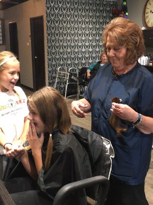 Greta McKee reacts to getting about nine inches of her hair cut off at Salon Enigma in Farmington Hills. Looking on is her friend Charlotte Mills; the stylist is Denise Cook. Greta donated the hair to be made into wigs for women battling cancer.
