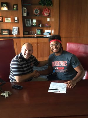 Theophilis James Harvey III (right) and Davenport men's rugby coach Harry King II shake hands after Harvey signed with the Panthers on June 19.