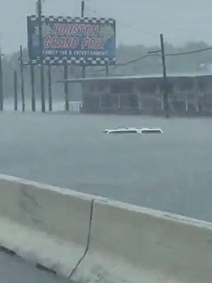 A car is almost submerged at an exit to a school near Humble, Texas.