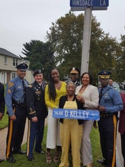 Vera Kelley (center) holds a street sign, which bears the name of her late son, Army major Dwayne Kelley, killed on a tour of duty in Iraq in 2008. The street he grew up on in Willingboro, Hinsdale Lane, was renamed in his honor. His wife Manita Seabrooks-Kelley (right), and daughter Mushirah Kelley (left) stand nearby as well as members of the New Jersey State Police and military officials.