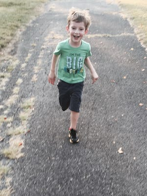 Paxton Sandrik, 4, smiles while running with his father, columnist Andy Sandrik. The key to teaching sports to young kids, Sandrik writes, is making them fun.