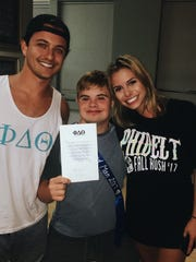 Arik Ancelin, who was born with Down syndrom, center, with Derek Stanley, left, president Phi Delta Theta fraternity at FSU, and Arik's sister, Ava Ancelin, right