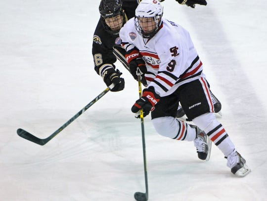 St. Cloud State's Joey Benik (9) carries the puck last