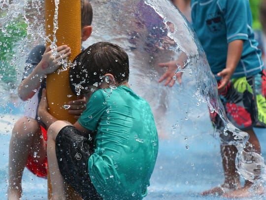 Children enjoy the fountains on the splash mat  at