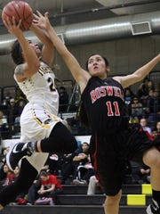 Audrianna Chenault, left, attempts a lay-up Tuesday night while being guarded by Roswell's Melanie Martinez.