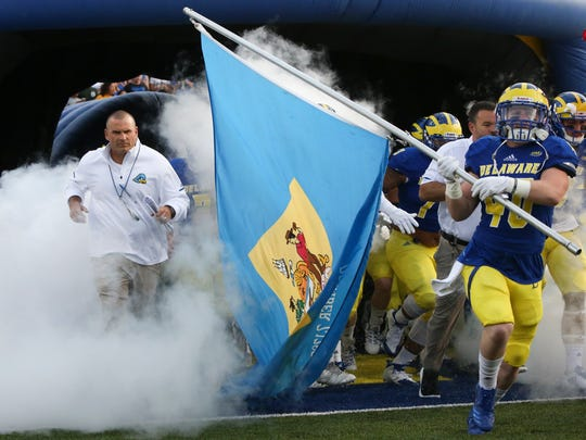 New head coach Danny Rocco runs out with his team as Pat Crowley carries the Delaware state flag before the Blue Hens' 22-3 win against Delaware State at Delaware Stadium.