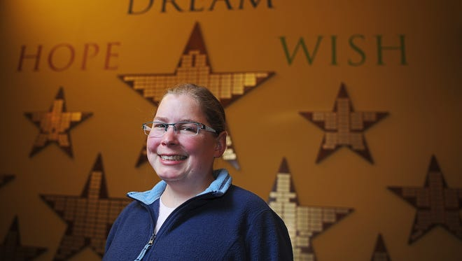 Kelsey Hoffman, a childhood cancer survivor, poses for a portrait Thursday at the Make-A-Wish Foundation of South Dakota office in Sioux Falls. Hoffman's wish as a little girl was to meet Garth Brooks, and the two have remained friends since.