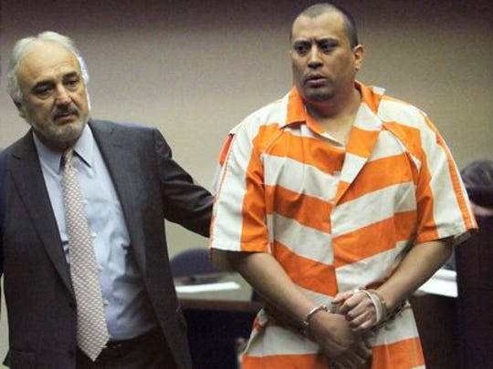 Luis Javier Solis-Gonzalez, right, is escorted out