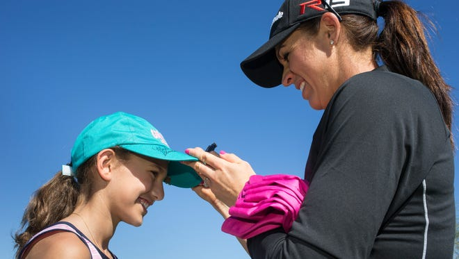 Nicole Castrale signs a hat worn by Talia Gutman at the 2015 JTBC Founders Cup Media day at the Wildfire Golf Club at J.W. Marriott Desert Ridge Resort and Spa.