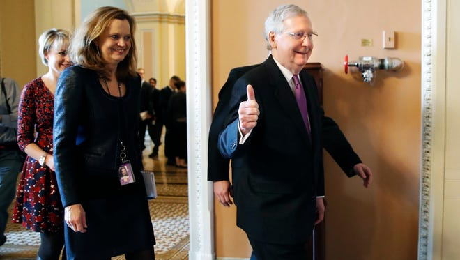 Senate Majority Leader Mitch McConnell gives a thumbs-up sign after reaching an agreement to end the government shutdown Monday.