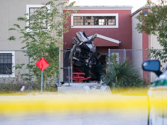 Lee County Sheriff's Deputies examine a car that went airborne and crashed into Evangelical Christian School at a high rate of speed  Wednesday, January 17, 2018, in Fort Myers. The driver of the car died in the crash.