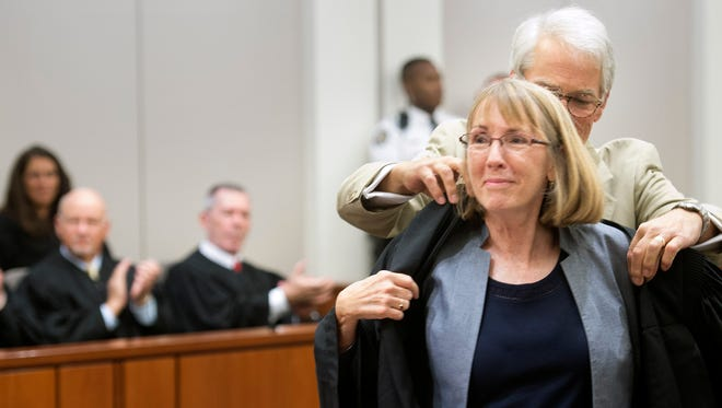 Christy Fawcett, left, is robed by her husband Rob, after she is sworn in.