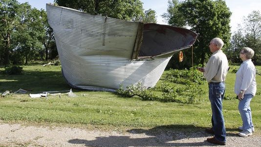 Georgette Bauman, right, shows her insurance agent Dennis Jungling, left, the grain bin that blew over her home and landed in her front yard near Clarksville, Iowa, Tuesday, June 17, 2014.