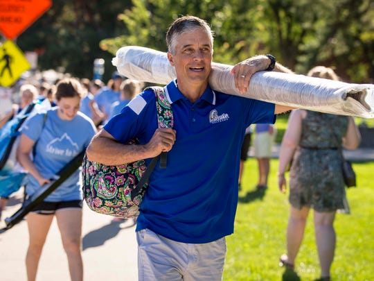 Drake University presidentMarty Martin helps move student's belongings into the dorms at Drake University in Des Moines, Iowa, Wednesday, Aug. 23, 2017.