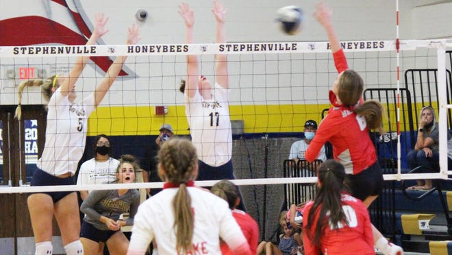Two Stephenville juniors, Landri Withers (5) and Emma Giddings (17) jump to block a shot during a recent home volleyball win over Lake Dallas.