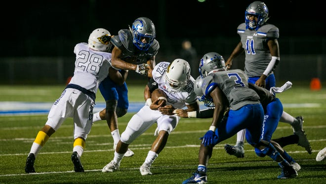 "Naples junior running back Cesare ""Chez"" Mellusi is brought down by Barron Collier on Friday, Oct. 27, 2017. Naples won with a final score of 16-15 at Barron Collier High School."