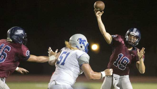 Roy Lopez III of Mesquite High School (51)  closes in on Perry High School quarterback Gabe Tomaszewski, right, during second quarter action at Perry High School, Friday, Aug. 28, 2015.