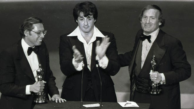 """""""Rocky"""" co-producers Irwin Winkler, left, and Robert Chartoff, right, flank Sylvester Stallone after receiving Golden Globes at the 34th Annual Golden Globe Awards in Los Angeles on Jan. 30, 1977. Chartoff, the Oscar-winning movie producer behind the boxing classics """"Rocky"""" and """"Raging bull,"""" has died. He was 81. Lynn Hendee, the president of his company Chartoff Productions, says Chartoff died Wednesday, June 10, 2015, at his home in Santa Monica, California. He had been suffering from pancreatic cancer."""