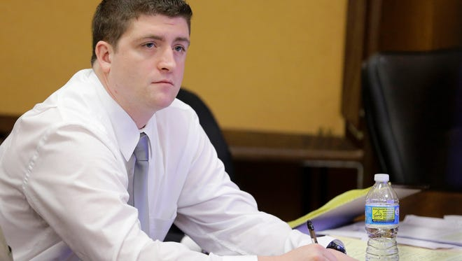 In this April 9, 2015 photo, Cleveland police Officer Michael Brelo listens to testimony during his trial in Cleveland.  A judge has reached a verdict in the trial of Brelo charged with voluntary manslaughter in the shooting deaths of two unarmed people in a 137-shot barrage of police gunfire.