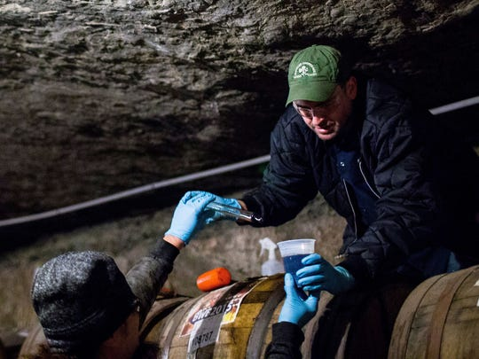 "Jason Heystek, Founders Brewing Company's Vice President of Planning, Packaging, Inventory & Logistics, passes a cup of Founders' ""Backwoods Bastard"" and a baster used to remove the craft beer from a barrel which the beer has been aging in since 2015 in a mine 85 feet underground at Michigan Natural Storage in Grand Rapids, Mich."