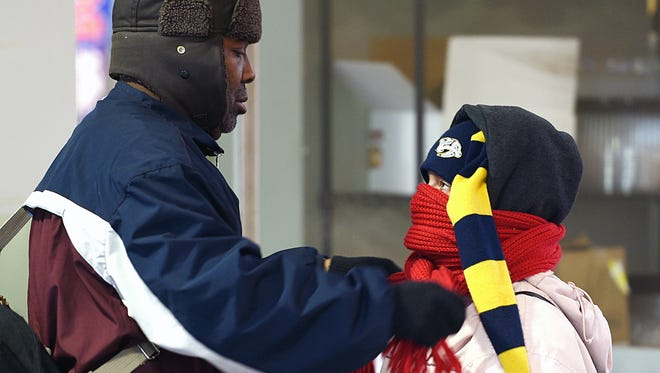Lamonte Jones wraps a scarf around his friend Victoria Boyd while waiting at the bus stop in 19 degree weather in downtown Nashville on Monday Jan. 11, 2016.