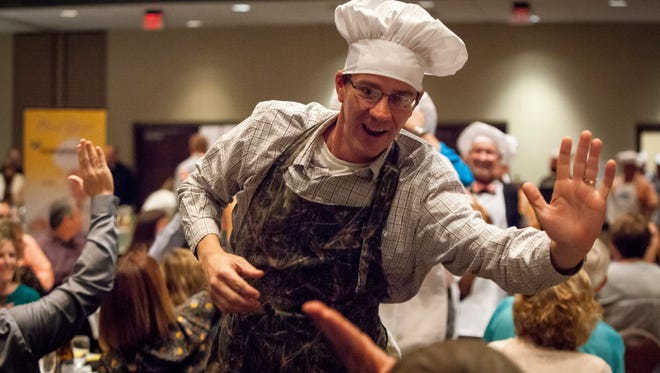 Cooks high five the audience at the Horizon Convention Center during the 2015 100 Men Who Cook event.