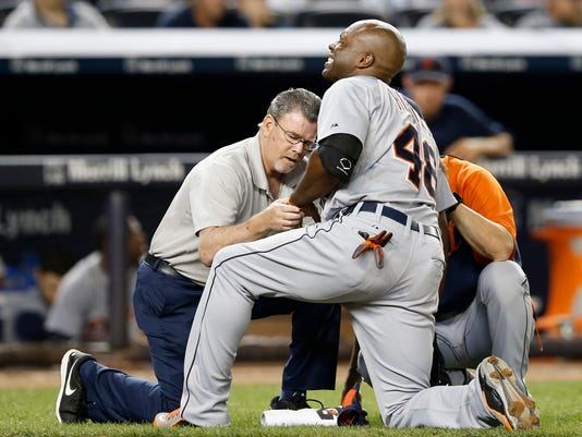 Detroit Tigers' Torii Hunter (48) is examined by a trainer after he was hit in the hand by a pitch thrown by New York Yankees' Dellin Betances in the ninth inning of a baseball game at Yankee Stadium in New York, Tuesday, Aug. 5, 2014. (AP Photo/Kathy Willens)