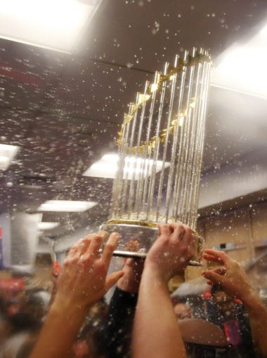 Astros players celebrate with the World Series trophy in the clubhouse.