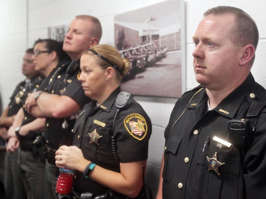 Warren County deputy sheriff Troy Black (right) and other deputies listen during a press conference as Sheriff Larry Sims talks about the shooting of a deputy at an apartment complex in Landen. The press conference was held at the sheriff's office in Lebanon.