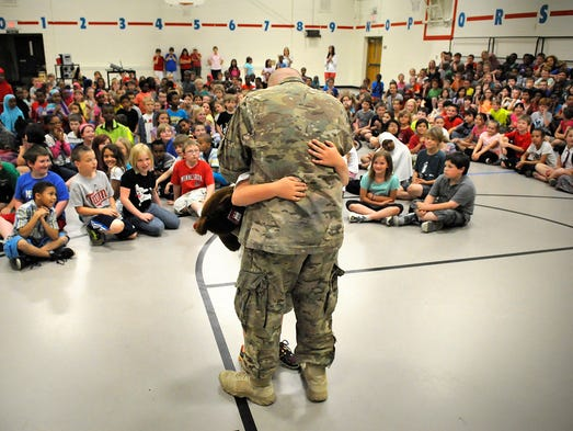 Sgt. Ryan Johnson and his son James embrace during an assembly at Madison Elementary Wednesday. Ryan Johnson surprised his son with an early homecoming after serving in Afghanistan.
