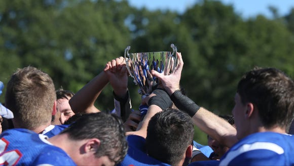 Pearl River players hoist the trophy after defeating