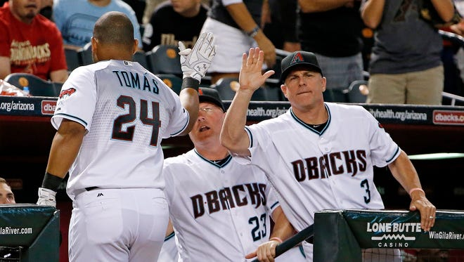 Arizona Diamondbacks' Yasmany Tomas (24) celebrates his home run against the Milwaukee Brewers with manager Chip Hale (3) and pitching coach Mike Butcher (23) during the second inning on Friday, Aug. 5, 2016, in Phoenix.
