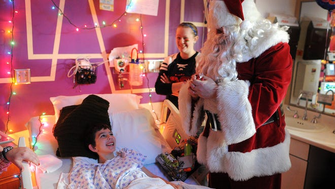 Sawyer Johnson, 9, of Sioux Falls cracks a smile Wednesday from his hospital bed at Avera McKennan Hospital and University Health Center as Santa Claus gives him a toy from Sioux Falls Firefighters Local 814.