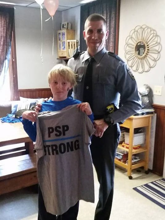 "Trooper Jon Colarusso brought Tyler Bryant a ""PSP Strong"" T-shirt and other gifts while visiting the ailing boy on Tuesday. Tyler's family and friends often wear ""Tyler Tough"" T-shirts in support of his fight."