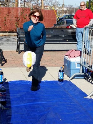 Susan Byrnes tosses a frozen turkey at some bowling pins at the York Rescue Mission Stuff-a-Truck event.